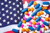 Multicolored prescription pills on American flag - 178010479