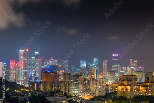 Skyscraper buildings and business downtown of Singapore at night scene Poster