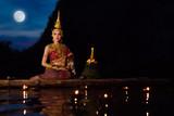 Piękna azjatykcia dziewczyna w Tajlandzkim tradycyjnym smokingowym obsiadaniu na spławowej tratwie w Loy Krathong festiwalu