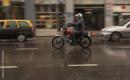 Fotobehang Buenos Aires Man riding a motorcycle in the rain