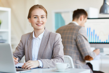 Happy businesswoman making notes in working diary with her colleague on background