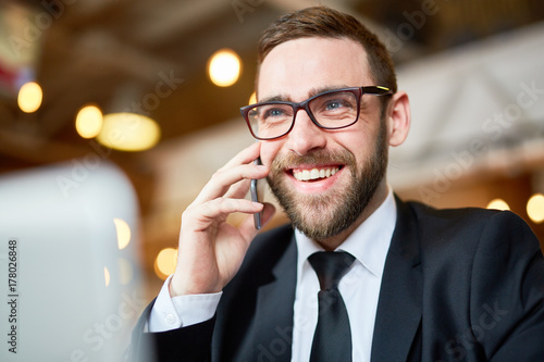 Sticker Joyful young businessman discussing joint project with colleague on smartphone while sitting at modern office, head and shoulders portrait