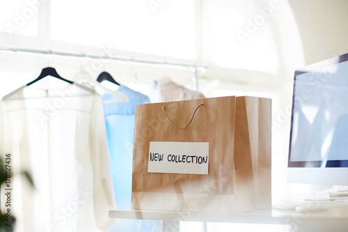 Paperbag named new collection on background of clothes on hangers Poster