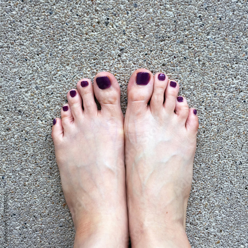 Fotobehang Pedicure Beautiful Nail, Close Up Woman's Bare Feet and Red Nail Polish on Cement Floor Background Great For Any Use.