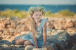Blond girl pretty with blue eyes wearing light dress with naked arms and legs and wild flowerrs wreath on top head posing in ancient city stones close to seaside beach with teddy bear