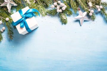 Christmas background on blue. Present gift box, branch and decorations top view.