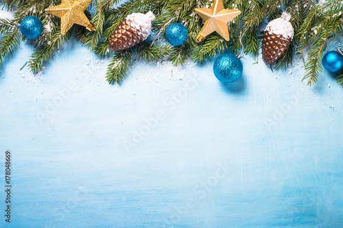 Christmas background on blue. Snow fir tree and decorations.