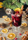 glass of hot mulled wine for the new year with ingredients for cooking, nuts and Christmas decorations - 178088203