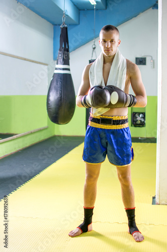 Young kick boxer with boxing gloves and towel around his neck in exercise hall Poster