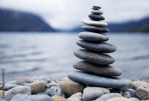 Zen balancing pebbles next to a misty lake. Poster