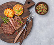 Sliced grilled beef barbecue steak with lemon, rosemary and spices on cutting board. Selective focus