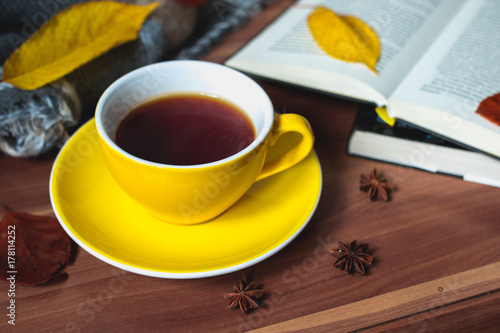 Yellow cup of tea with books and autumn leaves Poster