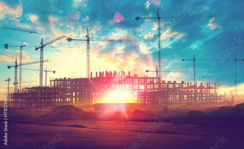 Sunset landscape.Construction cranes and buildings