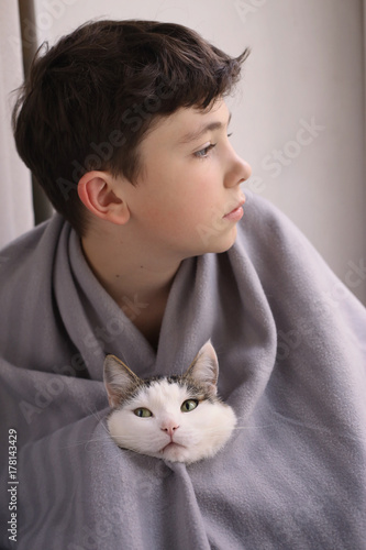 teenager  boy with cat wrap in rug close up winter cosy photo Poster