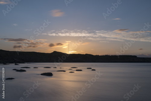 Foto op Canvas Zee zonsondergang silhouetted cliffs and bay at sunset