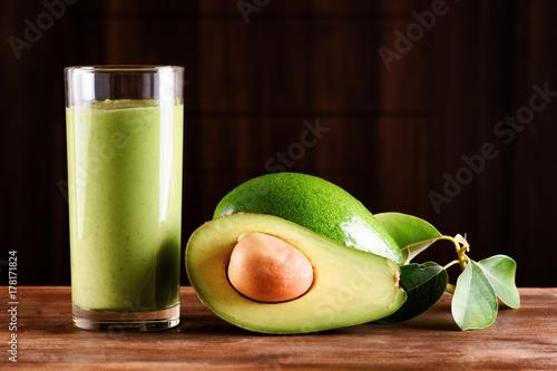 Fresh avocado smoothie and ripe avocado on wooden table