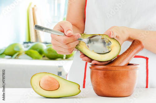 Woman making Mexican sauce Guacamole from fresh avocados