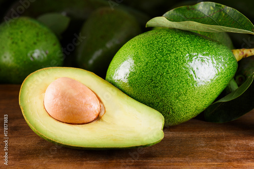 Ripe green avocado on wooden table. Freshly harvested fruits