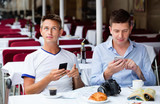 Two men sitting with coffee and looking at mobiles in cafe - 178180236