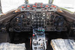 Old aircraft cockpit with steering wheels, control levers, and a