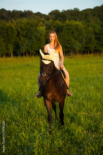 Active young woman ride a horse in nature Poster