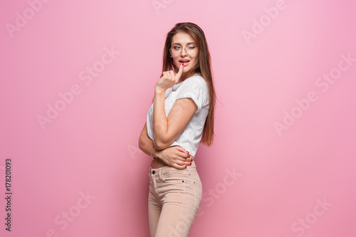Pretty young sexy fashion sensual woman posing on pink background dressed in hipster style jeans