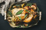 Oven roasted whole chicken with onion, apples and sage in serving tray over dark stone background, top view, selective focus. Celebration food concept - 178230204