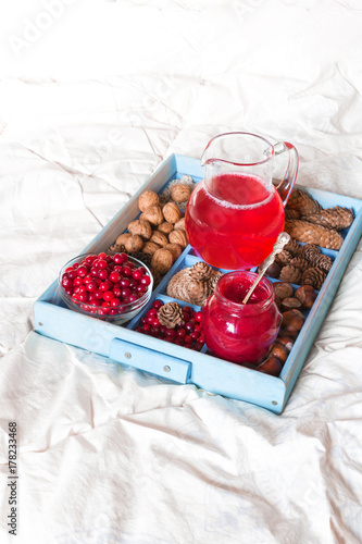 Poster Juice drink from berries of cranberries, jam and berries in a glass bowl on a tr