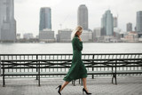 Thoughtful woman walks in her elegant dress along the river shore in New York - 178243880