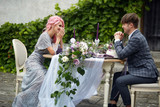 Laughing man and his lady with pink hair sit at the dinner table with pink decor - 178255063