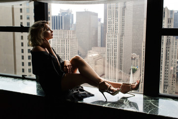Seductive woman in black silk robe sits on a windowsill looking at New York
