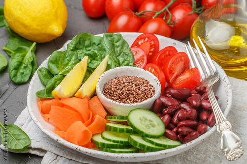 Foto op Canvas Boeddha Vegetarian buddha bowl. Raw vegetables - tomatoes, cucumbers, beans, spinach, carrots, lemon and flax seed in a bowl. healthy, detox food concept. Selective focus