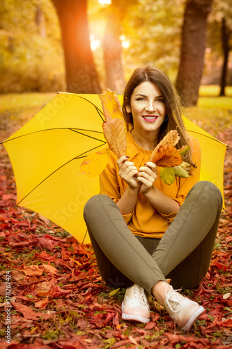 Juliste happy woman with umbrella walking in autumn park