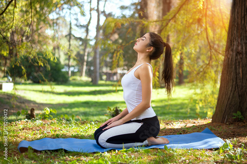 Fotobehang School de yoga Young beautiful woman practicing yoga in the park.