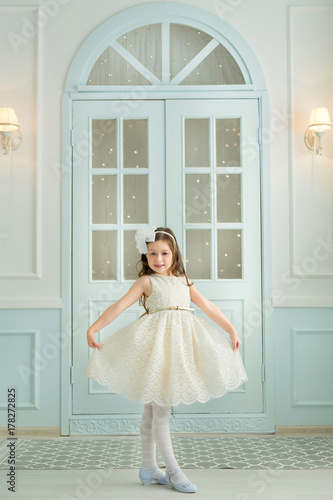 Plakát smiling beautiful baby girl in white dress in a light interior