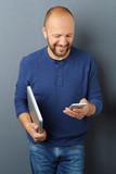 mann mit handy und notebook