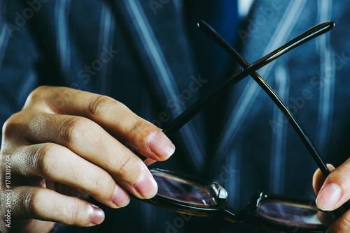 Plakat 眼鏡を持っているビジネスマンの手 クローズアップ スタジオ撮影