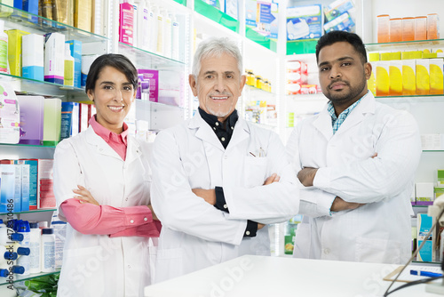 Multiethnic Pharmacists Standing Arms Crossed In Pharmacy