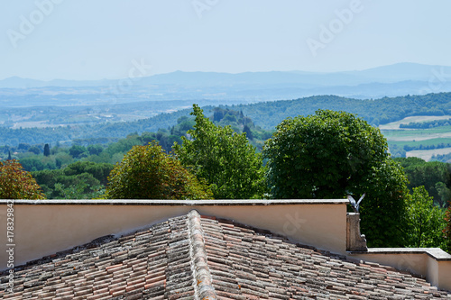 Deurstickers Toscane View of Tuscan hills over a tiled roof in Montepulciano, Italy