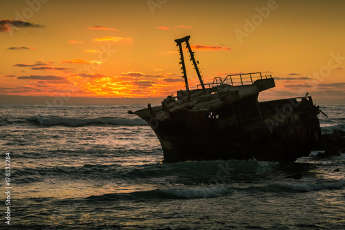 Fotobehang Zwart The wreck of a trawler lies on the rocks silhouetted against the golden light of sunset. Cape Agulhas, South Africa