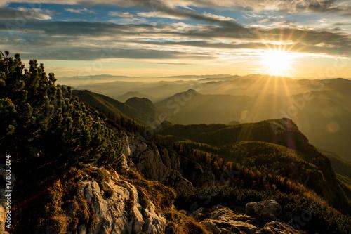 Fotobehang Zwart Herbstliches Abendrot auf einem österreichischen Gipfel mit Nebelschwaden in den Tälern
