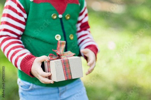 Little girl in elf sweater and hat waiting for a Christmas in the wood Poster