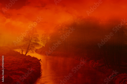 Fotobehang Rood traf. Fog of mist hovering over a small, winding river lit by red, morning sun