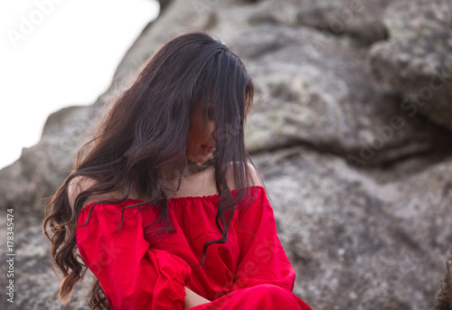 Plakát girl in red dress on rocks