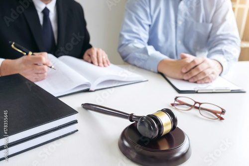Fototapeta Close up of gavel, Male lawyer or judge Consult with client and working with Law books, report the case on table in modern office, Law and justice concept