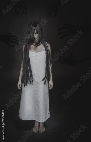 Mystical ghost woman with long black hair and shadow hands on dark Poster