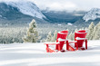 Snow Covered Red Adirondack Chairs Facing a Frozen Forested Valley on a Snowy Winter Day. Banff National Park, AB, Canada.