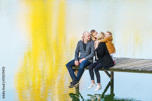 Plakat Family spending time together by the lake in autumn
