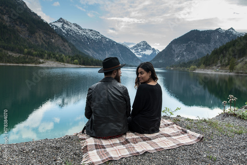 Hipster couple enjoys nature at a mountain lake in Austria Poster