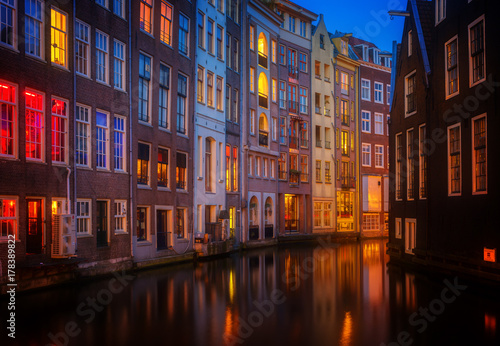 Foto op Plexiglas Amsterdam Illuminated houses over canal with reflections at night, Amstardam, Netherlands, retro toned
